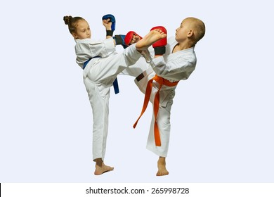 Girl in blue gloves and belt kick boy in red gloves