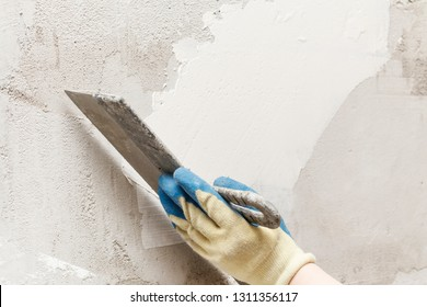 girl in blue gloves. review only a limb. putty putty on the wall. close-up.