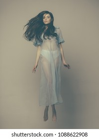 girl in blue gown jumping isolated on dimmed beige background. Young nymph in light silk dress flying in air. Lightness and levitation, airiness concept.
