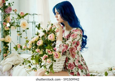 girl with blue hair standing on a bed in a vintage studio with flowers and a bed