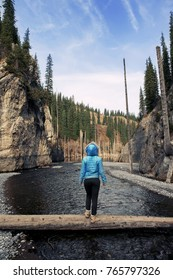 Girl in blue jacket standing in the middle of the river on log and enjoy the scenery