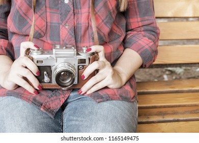 Girl in blue jeans and checkered shirt is sitting on the wooden bench and holding an old film camera in her hands. Toned.