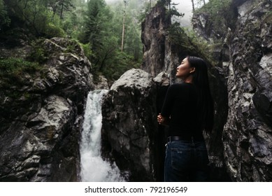 Girl in blue jeans in front of big waterfall