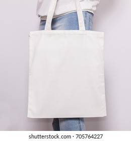 Girl in blue jeans holds blank cotton eco tote bag, design mockup.