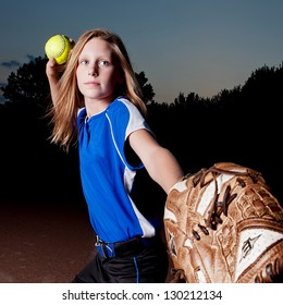Girl in blue jersey at night leading with mitt and throwing softball