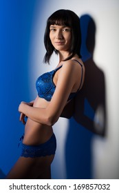 Girl in blue lingerie, standing against the wall