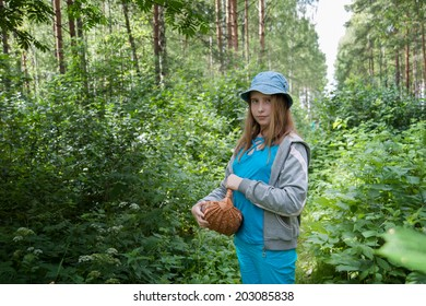 girl in blue Panama with a basket in the summer forest