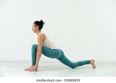 the girl in the blue pants and white t-shirt doing yoga in Studio on white background.