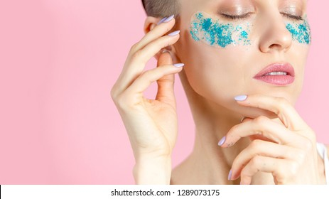 A girl with blue patches under eyes over pink background, morning beauty procedure concept