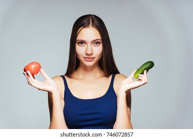 girl in a blue shirt holding a pair of vegetables