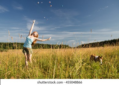Girl in a blue shirt on the nature in the field with the dog doing exercises and enjoying life