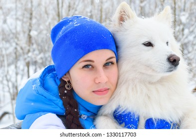 Girl in a blue ski suit hugs and strokes a Samoyed Husky dog Samoyed Spitz.