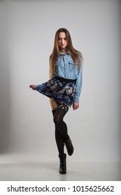 A girl in a blue skirt and a denim shirt