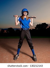 Girl in blue softball uniform at night with bat across shoulders.