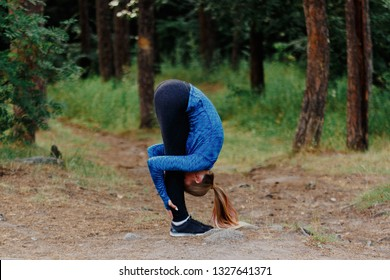 Girl in blue sportswear doing exercises outdoors in coniferous forest. Standing forward fold. Healthy lifestyle sport concept