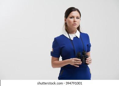 Girl in a blue suit. Keep a binoculars in his hands. Makes gestures.