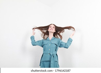 girl in a blue suit on a white wallbackground. Fashion catalog dynamic photography of a young brunette girl, on a background of white texture. Stylish every day office outfit. Free space for text