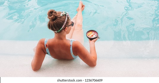 Girl in blue swimsuit eating acai smoothie bowl in pool in Bali