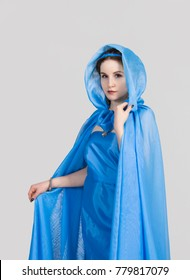 The girl in the blue tunic and cloak,in the Greek style, posing on a gray background. Studio shot, isolated image.