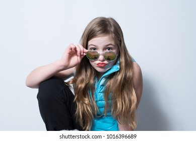 Girl in blue vest with pouty lips peering over round reflective sunglasses on white background