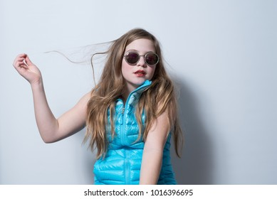 Girl in blue vest wearing round reflective sunglasses with indifferent, bored look on white background