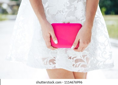Girl in blue white with pink bag clutch. Fashion Clothes Accessories Set. girl in a white dress is holding a small pink bag in her hands