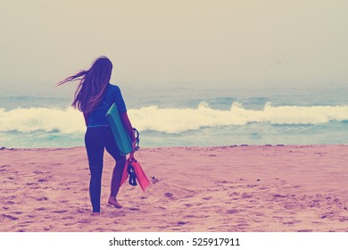 A girl with a board goes on the bank of ocean.