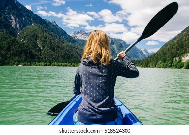 Girl in a boat rowing on a beautiful green lake surrounded by mountains and a forest on a sunny day