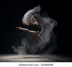 Girl in body jumps in dust cloud black background