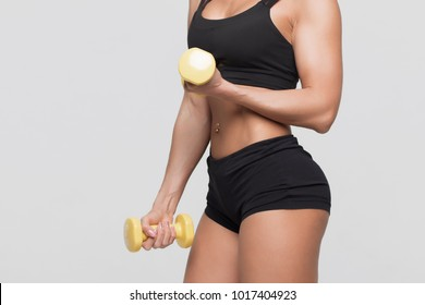 Girl bodybuilder on a gray background with dumbbells in hands