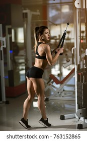 A girl bodybuilder trains in the gym. Beautiful young woman doing exercises in the gym .