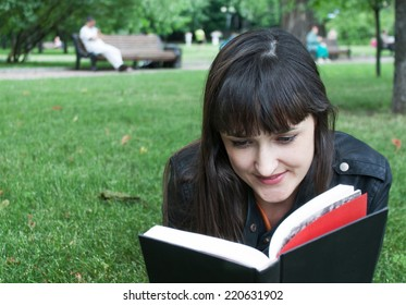 girl with a book on the grass
