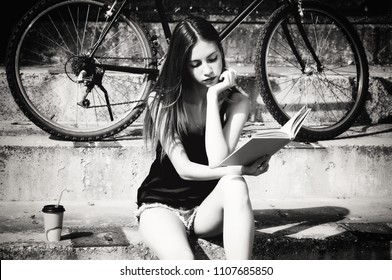 Girl with book sitting on stairs. Black and white photo