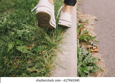 Girl in boots going on grass in park