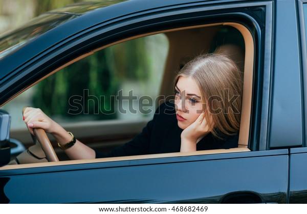 Girl bored in her car in traffic jam