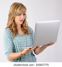Girl Bothered by Website. Thirteen year old girl holding a laptop and making a surprised/disgusted face while looking at the screen. Note: Not Isolated.