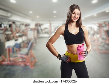 A girl with a bottle in the gym