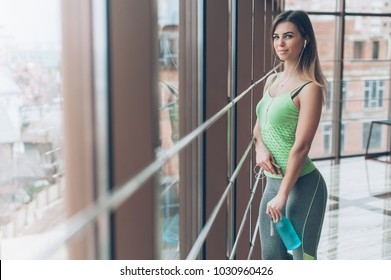 Girl with a bottle of water by the window in the gym