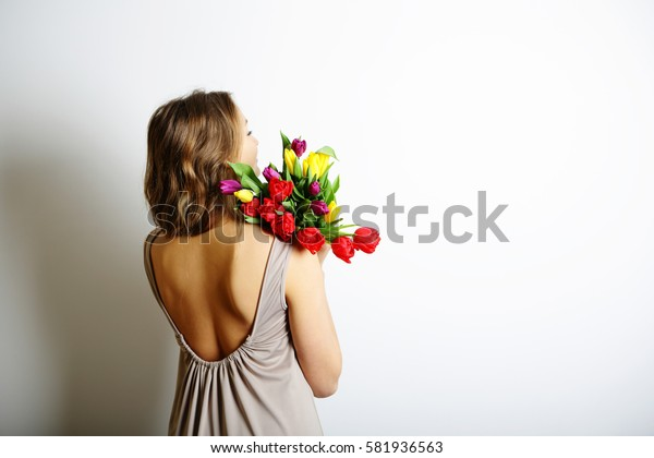 Girl with a bouquet of tulips on the shoulder, standing in the open back dress