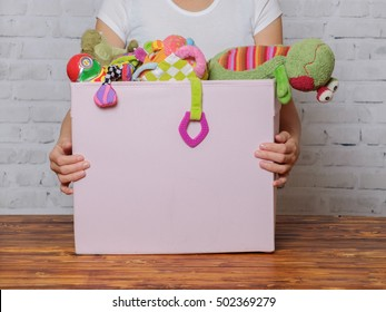 Girl with box of toys ready for donation