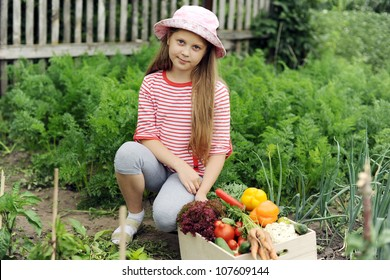 A girl with a box of vegetables in the garden