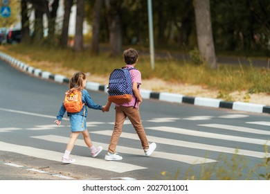 girl and boy with backpacks carefully cross road on pedestrian crossing on their way to school. Traffic rules. Walking path along zebra in city. concept of pedestrians crossing pedestrian crossing.