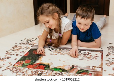 Girl and boy collect puzzle on the floor in the house