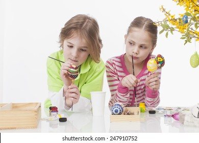 Girl and Boy colouring easter egg, smiling