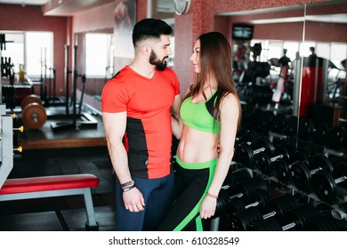 Girl and boy doing sports in the gym. Fitness models. Sports models do exercises with dumbbells. Sports guy and girl