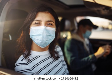 A girl and a boy driving in a car during coronavirus quarantine wearing medical masks. Safe taxi and healthcare during pandemic covid-19. Passangers virus safety concept