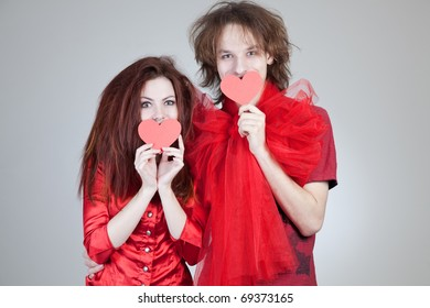 Girl and boy holding paper hearts, studio isolated shot