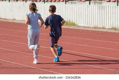 girl and boy jogging on tartan track