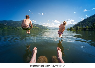 girl and boy jumping in lake water at summer holiday