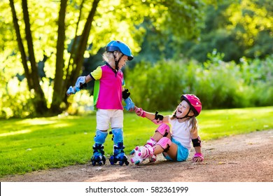 Girl and boy learn to roller skate in summer park. Children wearing protection pads and safety helmet for safe roller skating ride. Active outdoor sport for kids. Siblings help and support each other.